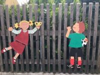 Bunte Holzfiguren zieren den Zaun